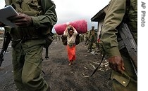 A woman flees to escape fighting between U.N.-backed government forces and renegade troops in the village of Sake in eastern Congo, 28 Nov 2006