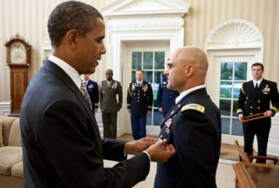 President Barack Obama presents White House Military Aide LTC Barrett Bernard with the Defense Superior Service Medal during a departure ceremony in the Oval Office, Oct. 12, 2011