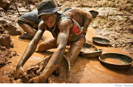A gold miner scoops mud while digging an open pit at the Chudja mine in the Kilomoto concession near the village of Kobu, 100 km (62 miles) from Bunia in north-eastern Congo